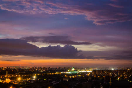 Multi-colored sky with clouds at sunset over the night city photo
