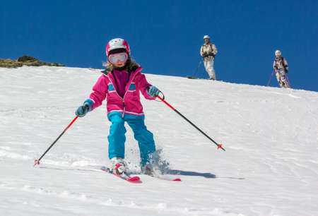 Girl on skis in soft snow on a sunny day in the mountains, on a steep slope  Stock Photo