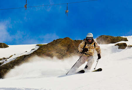 Skier in the deep snow  Against the background of the cliff  Raises the snow dust