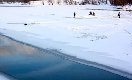 People on ice fishing at sunset  Thin ice on a pond Stock Photo - 16836882