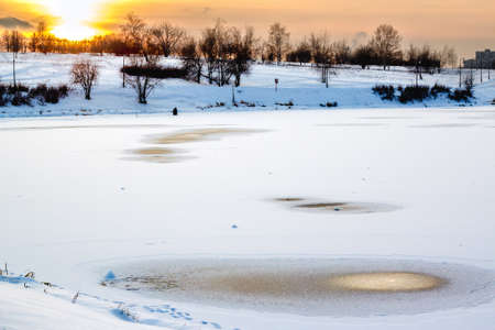 Man ice fishing alone on the pond at sunset photo
