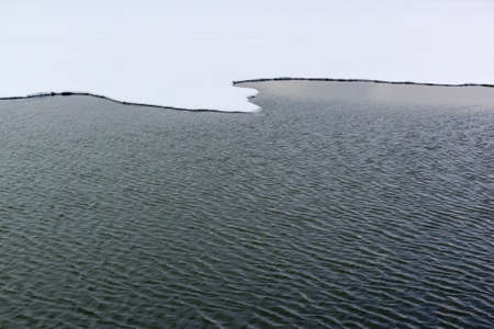 Sinuous edge of the ice field in the snow and the area of open water Stock Photo - 18410535