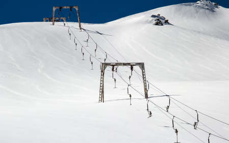 Old ski lift at a ski resort in the mountains powdered with snow. Mechanised system for transporting skiers and snowboarders uphill