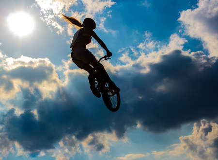 Silhouette woman cyclist flying in the sun and cloudy sky
