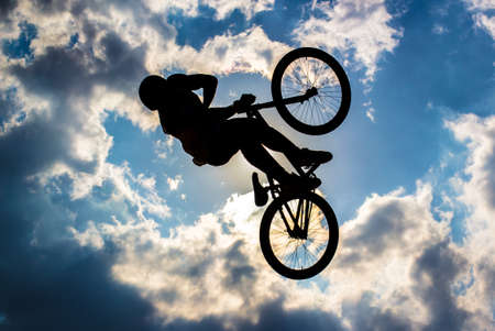 Silhouette of a cyclist flying in background the sun and blue sky with clouds