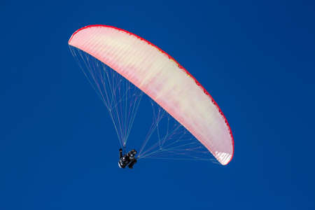 Red Paraglider against a cloudless blue sky on a sunny day