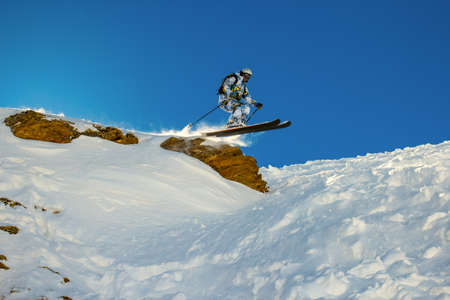 Skier jumps from a cliff during fast motion  Backlight of the sun