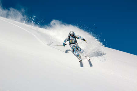 Skier on a steep mountain slope  In turn raises the snow dust