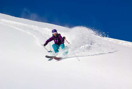 Woman Skier on a steep mountain slope  In turn raises the snow dust  Stock Photo