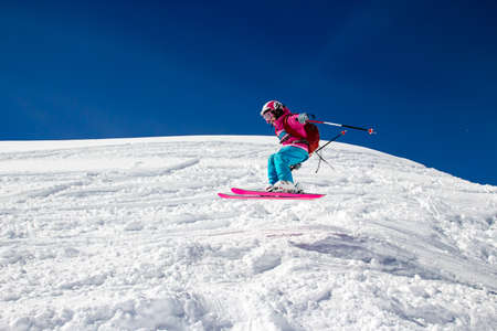 Little girl with a big backpack on skis in flight over the snow Stock Photo