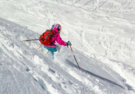 Little girl with a big backpack on skis in deep snow on a steep slope Stock Photo