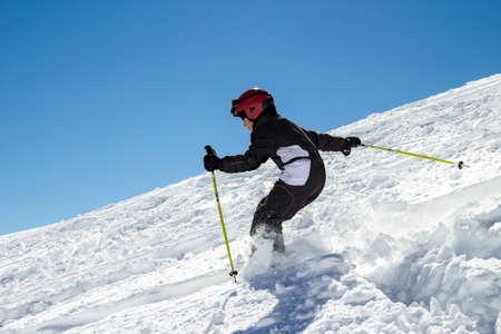 ski�r: Weinig jongen op ski's in diepe sneeuw op een steile helling Stockfoto