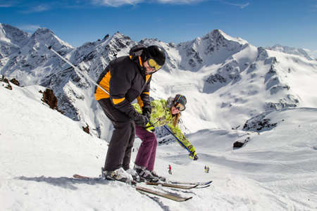 Adult  happy couple  man and a woman are standing on skis at a ski resort before going on the background of high mountains and blue sky with clouds  In sunny weather