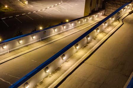An empty parking lot at night illuminated entry bright lights