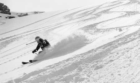 Woman skier at high speed in deep snow in a turn raises the snow dust