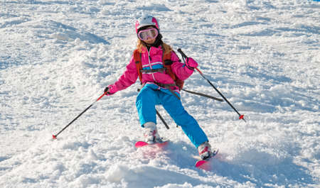 moguls: Little girl quickly downhill the bumpy slope in ski resort