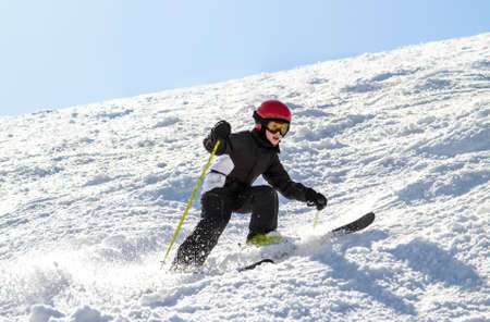 Little boy on skis on a bumpy slope at a ski resort Stock Photo
