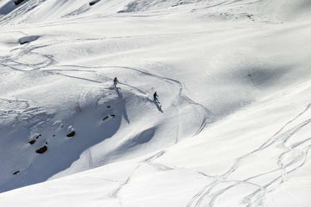 Pair of skiers on the slopes of the wild in the mountains Stock Photo