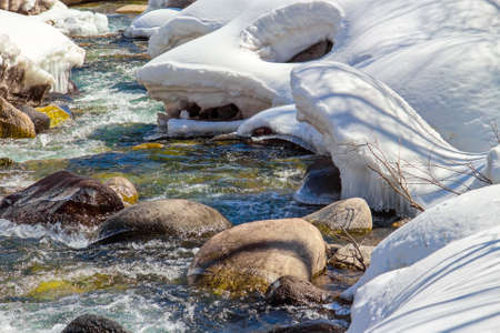 Fast mountain river with stones in the early spring to the shores covered with melting snow