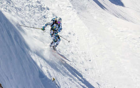 Skiing in the sunlight at high speed on an extremely steep slope Stock Photo