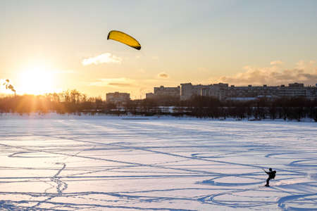 Snowkiting on a frozen pond in the park on trees background at sunset