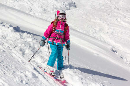 Little girl on skis plastered with snow