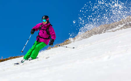 Skier on mountain slope on a clear blue sky  In turn raises the snow dust  Stock Photo