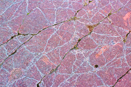 Abstract white pattern on the old stone. Texture of pink old stone in the cracks filled with soil and mos Stock Photo