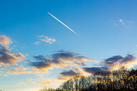 Bright white trail aircraft in the cloudy sky at sunset Stock Photo