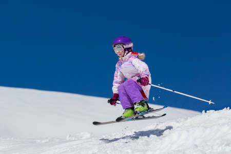 Little girl skier soars over a slope in a jump