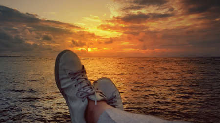 White sneakers of a man who admires the sea and the sky with a reddish glow in the island of Okinawa, Japan
