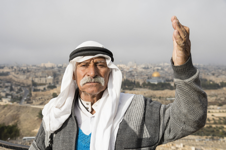 JERUSALEM, ISRAEL - December 16 2016: Arab man wave to peace against the Temple Mount and lift his arm