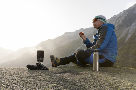 Hiker eats an apple during a break and prepares a hot tea Banco de Imagens