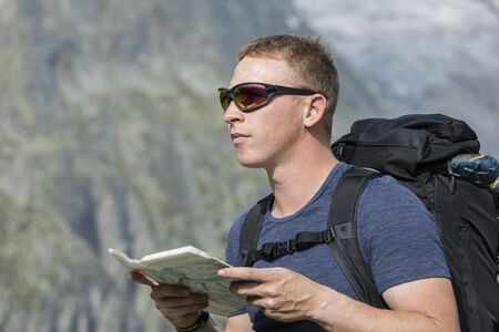 Hiker looks for the right way with the help of a map