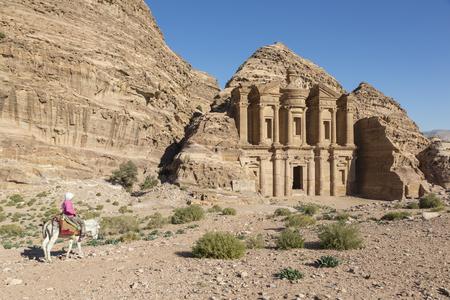 Ad Deir, Jordan December 25th 2015: Girl rides a donkey in front of the Monastery Al Deir in Petra, Jordan Editorial
