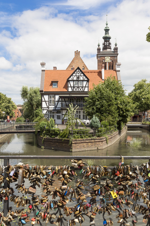 Danzig, Poland - July 7 2016: View of many love locks at the Love Bridge and Millers House at the Mill Island in Gdansks Old Town in Poland