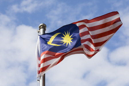Malaysia flag also known as Jalur Gemilang wave with the blue sky. People fly the flag in conjunction with the Independence Day celebration or Merdeka Day. Stock Photo