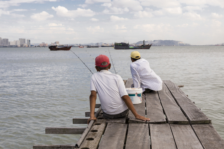 Penang, Malaysia, December 19 2017: Two Fishermen waiting for the catch of day on the wooden jetty in Georgetown 에디토리얼