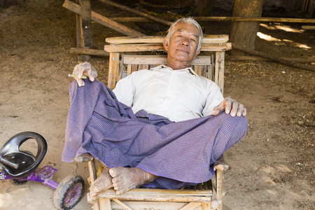 Bagan, Myanmar, December 27, 2017:  Senior man recovers in an armchair and smokes a cigarette Editorial