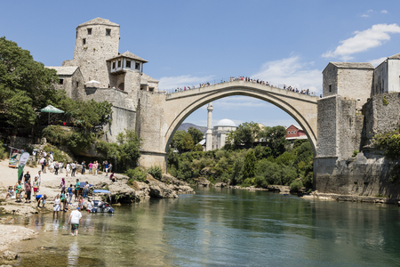 Mostar, Bosnia and Herzegowina, July 15 2017: Tourists enjoy the view of the historic arch bridge over the neretva river in Mostar on a beautiful summer day