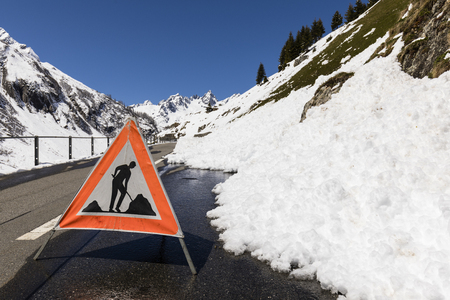 Warning sign because of a road blocked by a snow slide in the Alps