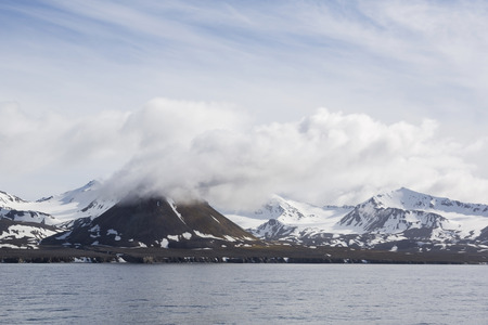 Landscape with snowy mountains on a sunny day seen from the sea in Spitsbergen, Norway Stock Photo