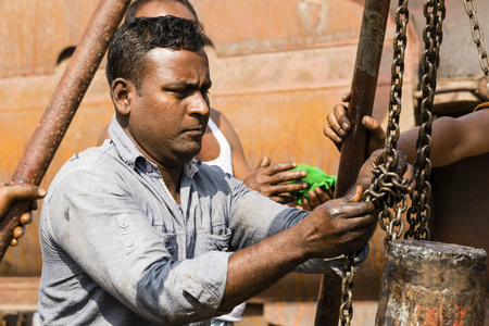 Dhaka, Bangladesh, February 24 2017: Worker at a shipyard in Dhaka Bangladesh, with their oil-smeared hands, attach a chain around the drive axle of a ship.
