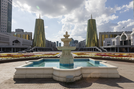 Astana, Kazakhstan, August 2 2018: The construction of glass and concrete on the main square, called the golden tower and a view of the complex of administrative buildings and fountain