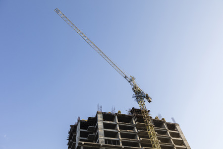 Construction crane with high-rise building under construction