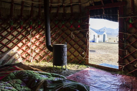 Interior shot of a traditional yurt with stove at Song Kul lake in Kyrgyzstan