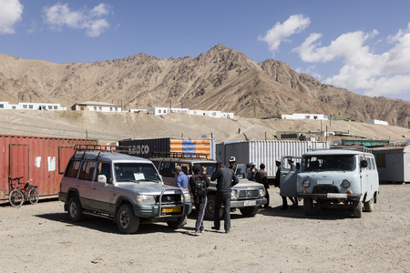 Murghab, Tajikistan, August 23 2018: Parking with cars in front of the market in Murghab on Saturday morning. The sales stands are in old containers Editorial