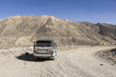 Langar, Tajikistan, August 23 2018: Off-road car is waiting on the Pamir Highway on the Pamir River. In the background are the mountains of Afghanistan Editorial