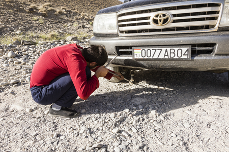 Langar, Tajikistan, August 23 2018: Repair of a flat tire on the Pamir Highway near Langar in the border area between Tajikistan and Afghanistan Editorial