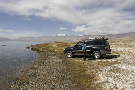 Karakul, Tajikistan, August 22 2018: Car with driver at the Karakul lake near Karakul town in the pamir mountains in Tajikistan